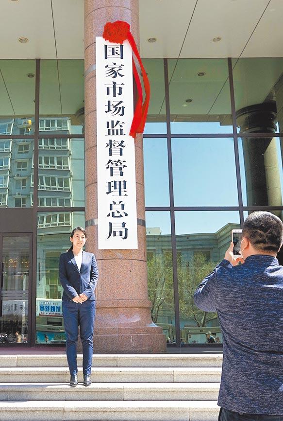 2018年4月10日,大陸國家市場監督管理總局在北京正式掛牌。圖為民眾與新牌合影。(中新社)