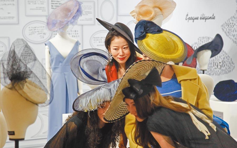 大陸消費市場持續快速成長,圖為上海時髦的女士在試戴禮帽。(中新社)