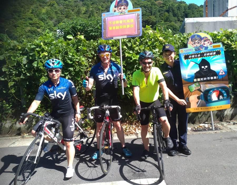 北投警分局在自行車騎士時常出遊的陽明山景點,宣導自行車下坡注意事項,遇到2名外籍騎士對於員警熱心宣導感到又驚又喜。(北投警分局提供)
