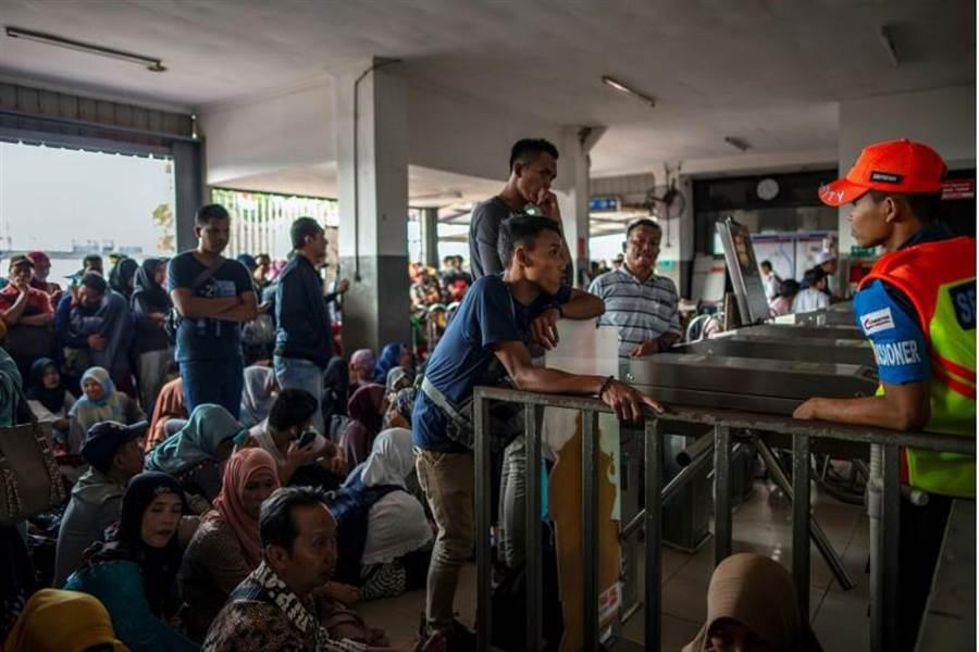 雅加達地鐵停擺,一些通勤者無奈在地鐵入口處等候。/路透社