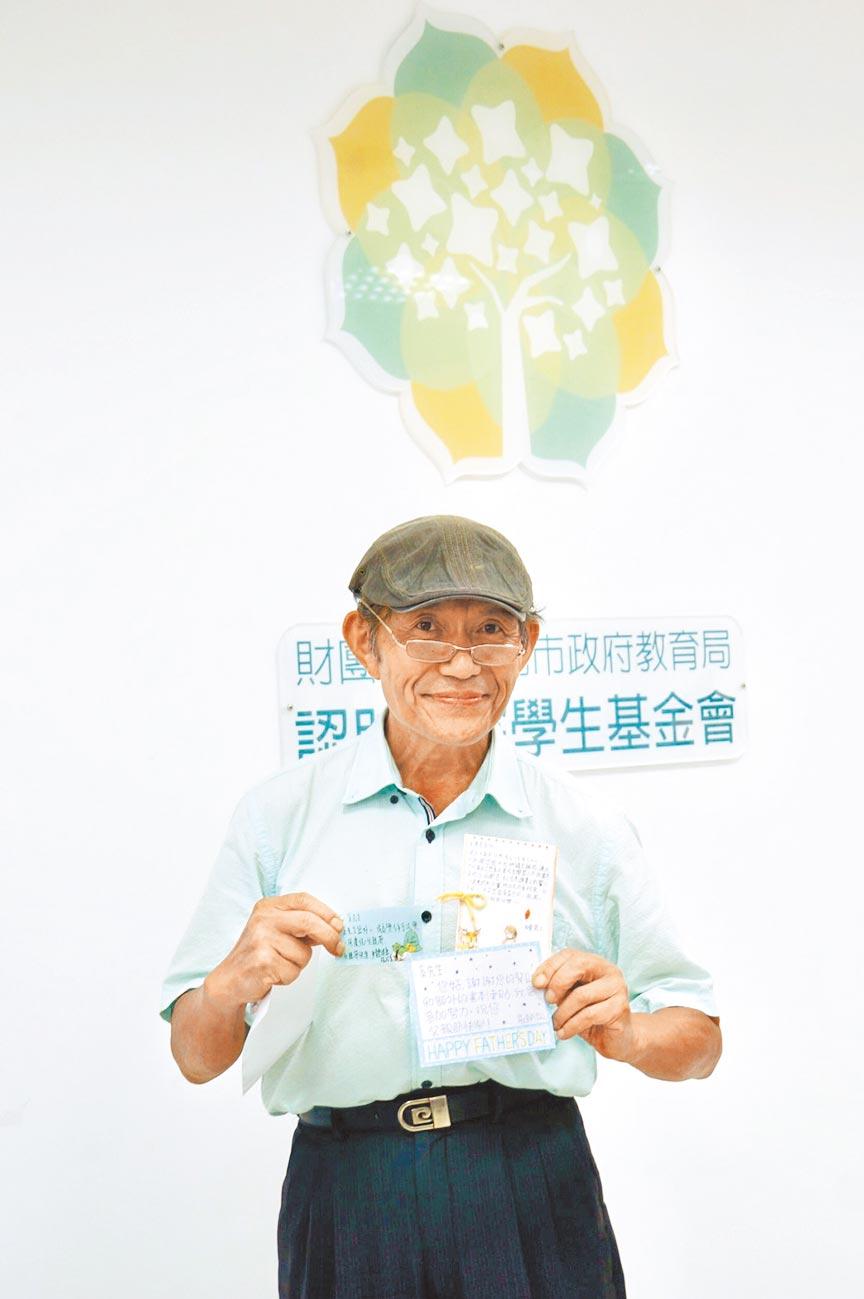牙醫師奚臺陽認助了5位國高中學生的學費,他開心 展示學生送給他的卡片,過了一個特別有意義的父親節。(張潼攝)