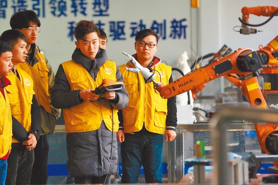 濟寧的山東省智能機器人應用技術研究院,幾位實習的大學生在研究如何操作機器人。(新華社資料照片)