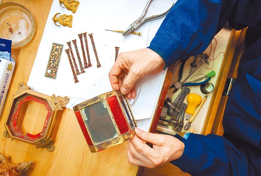 王津在工作台上拆解需要修復的鐘錶。(新華社)