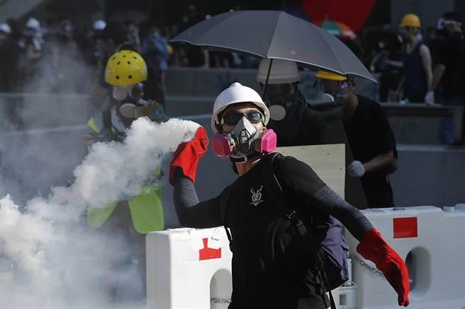 香港抗議群眾把警方射出的催淚瓦斯罐再擲回警方,目前已至少有82人因各種罪名被警方逮捕。(圖/美聯社)