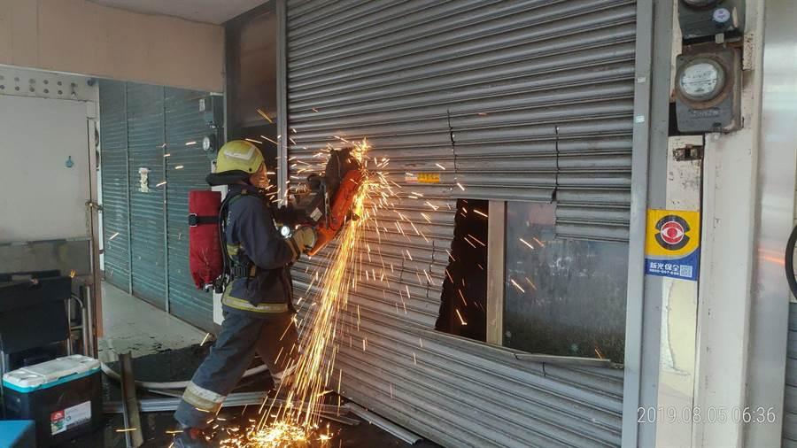 竹南鎮民族街一棟民宅5日上午發生火警,消防人員以砂輪鋸開鐵捲門進入搶救。〔謝明俊翻攝〕