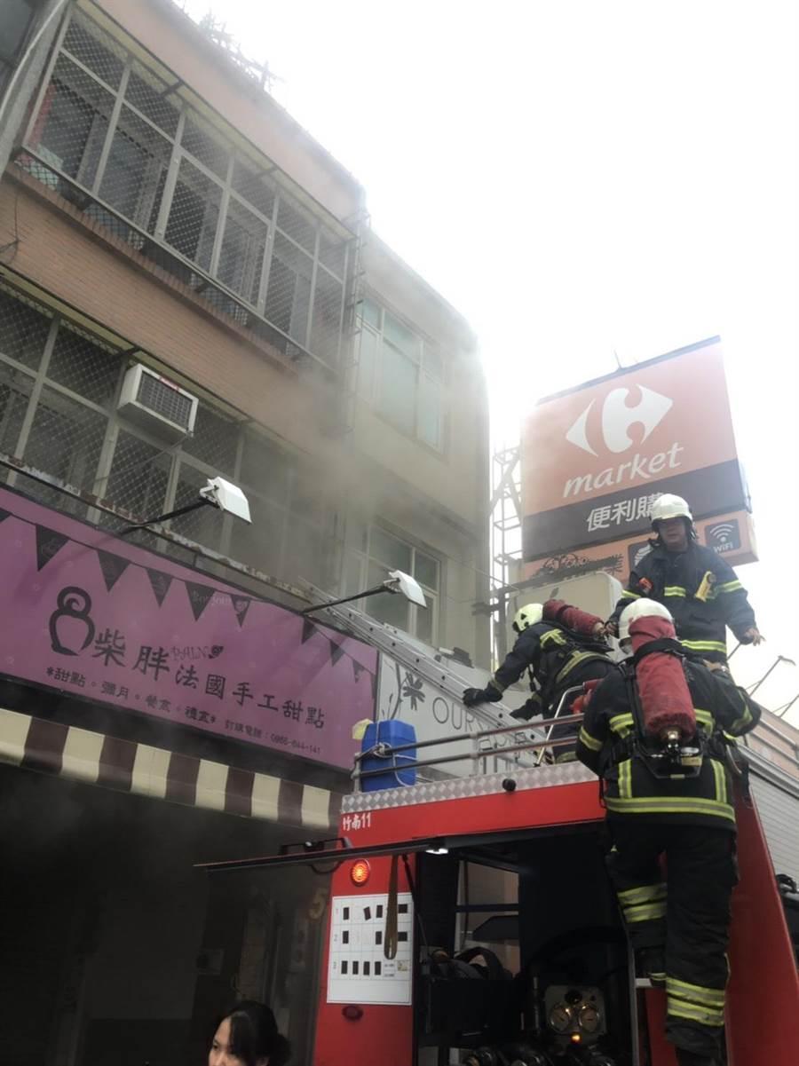 竹南鎮民族街一棟民宅5日上午發生火警,消防人員從消防車架梯從2樓佈線搶救。〔謝明俊翻攝〕