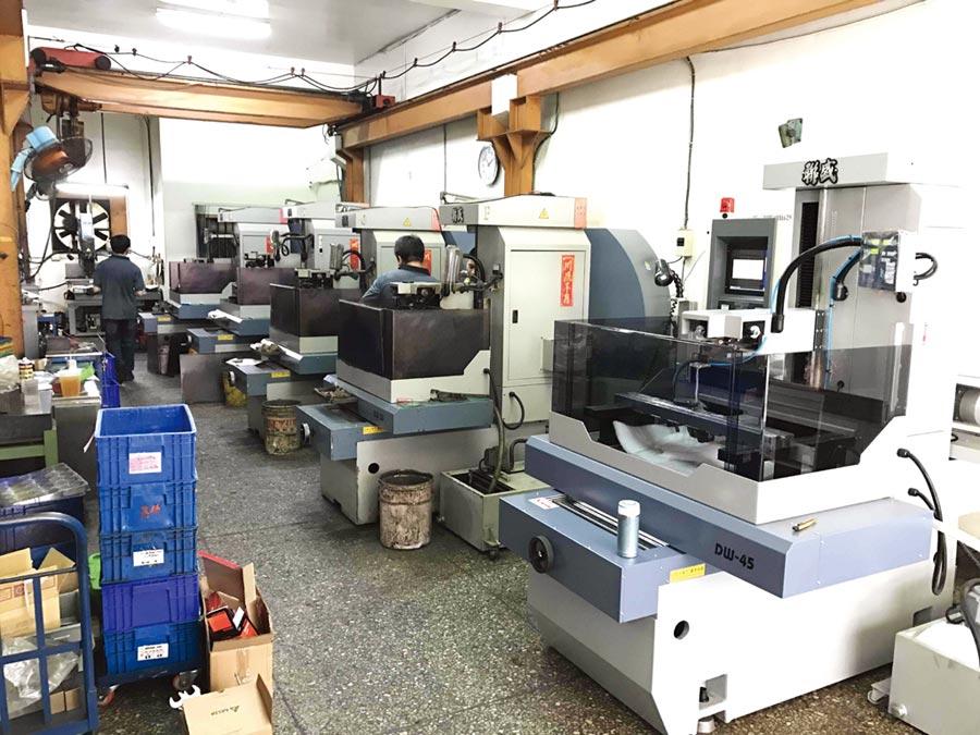「中走絲線切割機」市占第一名的聯盛機電公司,在客戶眼中設備好用、品質好、價格平實,隨著客戶訂單成長陸續訂購;圖為客戶廠內整排的中走絲線切割機。圖/王妙琴