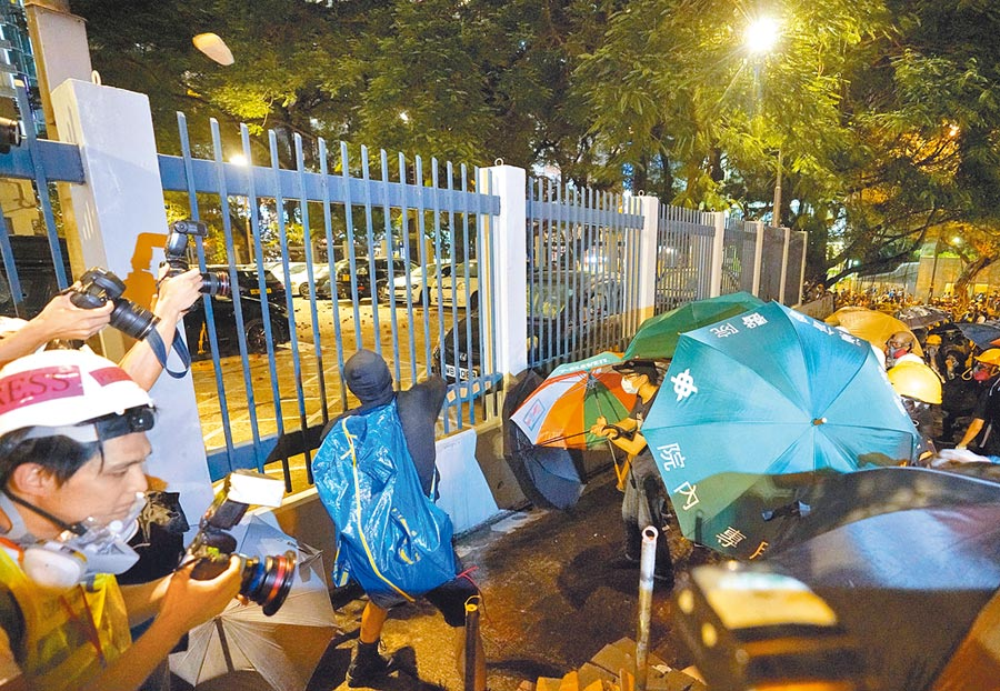 8月3日晚,示威者向尖沙咀警署內投擲磚塊,損壞汽車等財物。(中新社)