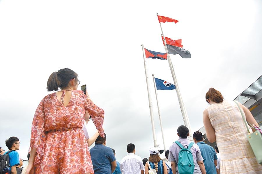 8月4日上午9時,上百名香港市民自發前往尖沙咀天星碼頭舉行升國旗儀式。(中新社)