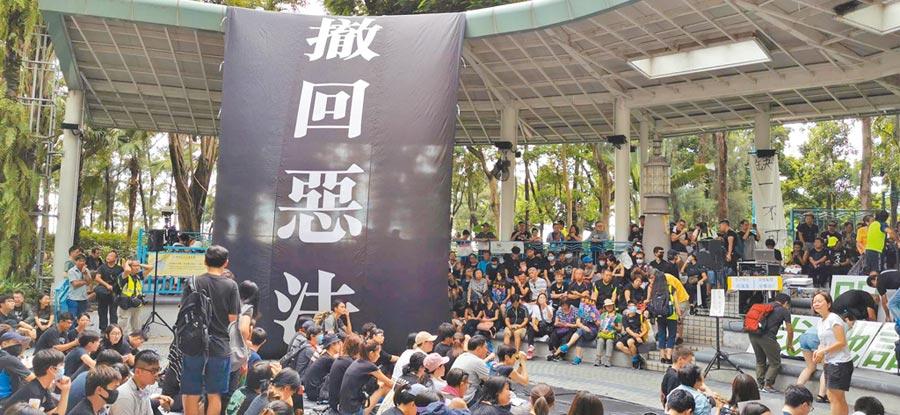 香港西環4日傍晚有「反送中」集會,地點臨近中聯辦,圖為準備參加集會的港人以及大會主台懸掛的「撒回惡法」巨型布條。(中央社)