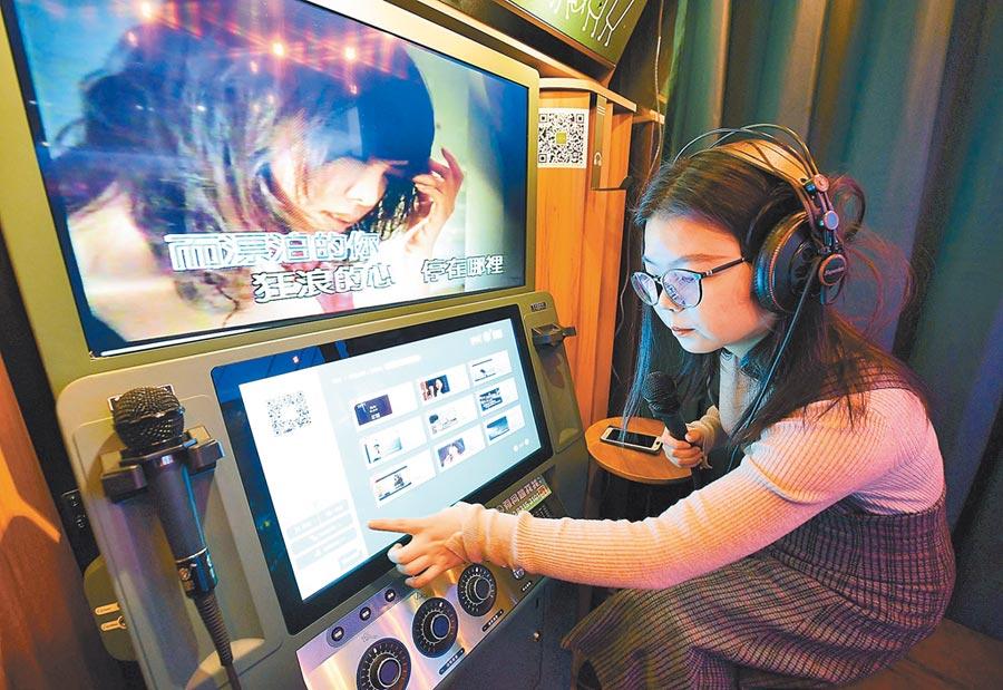大陸單身人口規模突破2億。一名女孩在西安曲江一家迷你ktv內點歌。(新華社)