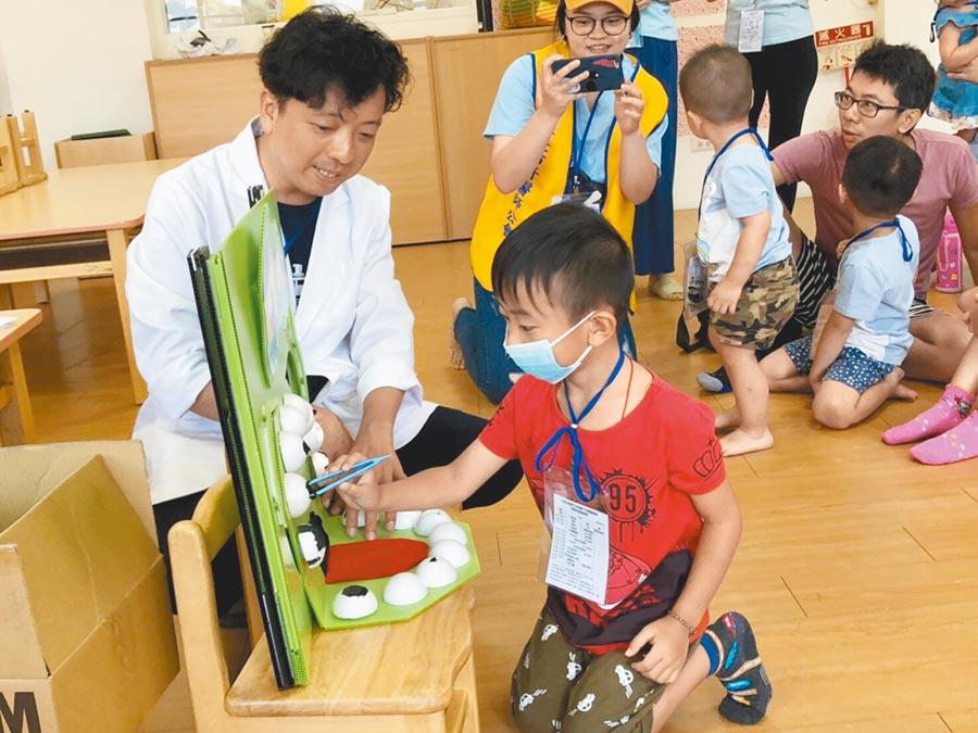 基隆市幼兒親子牙醫體驗營,小朋友扮演牙醫體驗拔蛀牙。(許家寧翻攝)