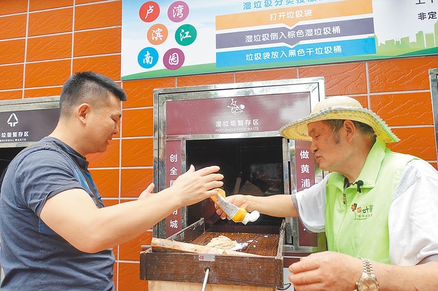7月3日,在上海市黃浦某社區,志願者幫助居民用乾濕分離器對濕垃圾進行分類投放。(新華社)