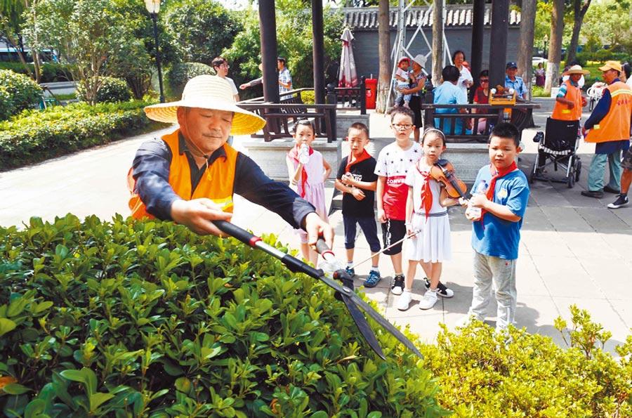 園林工人向小朋友們展示如何修剪灌木叢。