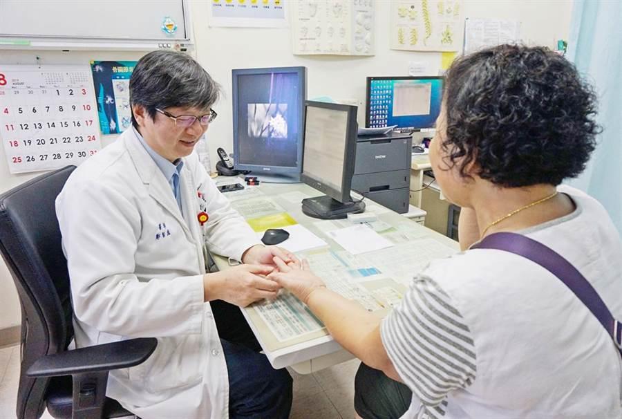 新竹馬偕骨科主任鄭智庭,為病患檢查手部肌腱是否能正常彎曲。(羅浚濱翻攝)