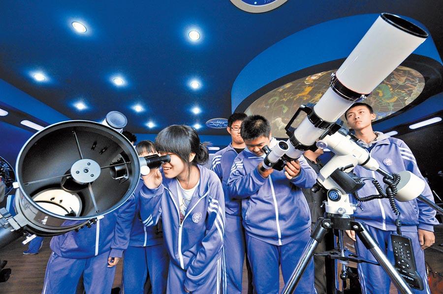 天津學生們在南開大學天文教室裡使用天文望遠鏡。(新華社資料照片)