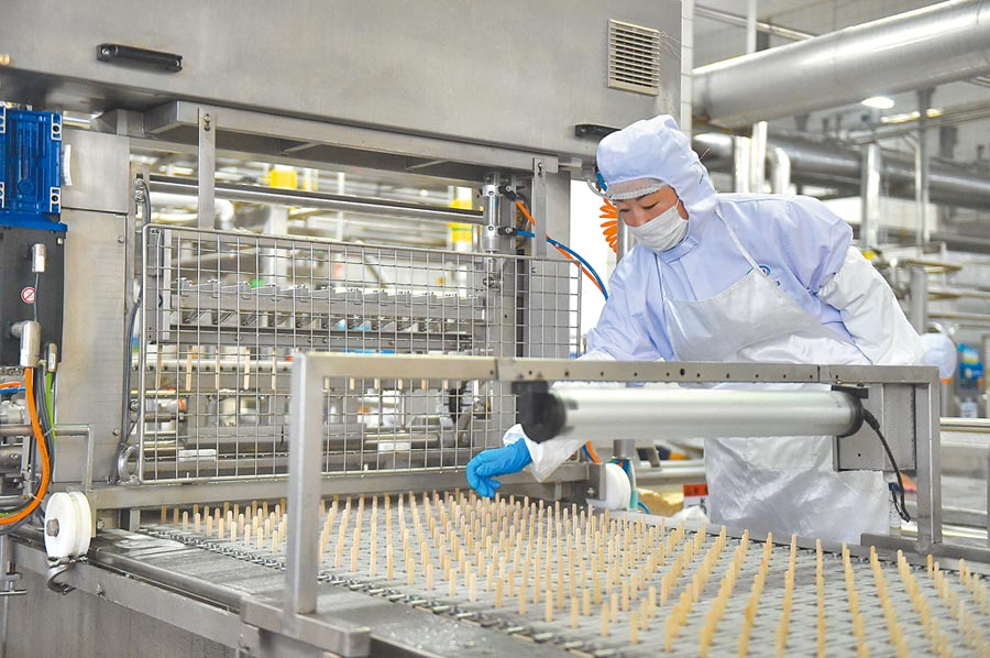 內蒙古呼和浩特的雪糕工廠,工人在雪糕插筷生產線上查看。(新華社資料照片)