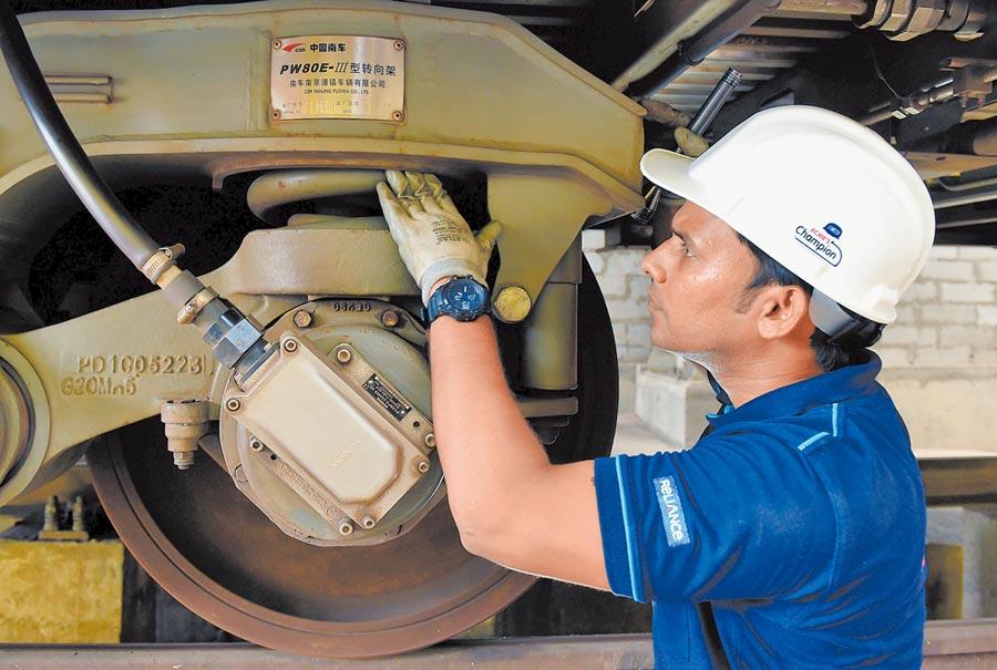 印度孟買,一名印度工作人員在例行查驗列車。(新華社資料照片)