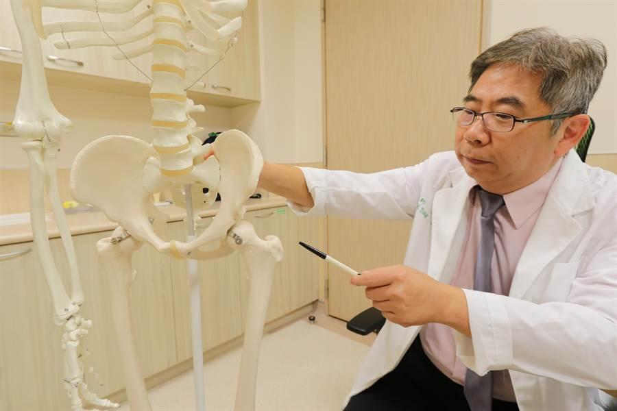 亞大醫院骨科部主任唐國民在人體骨骼標本上,指出患者患部位置。(林欣儀攝)