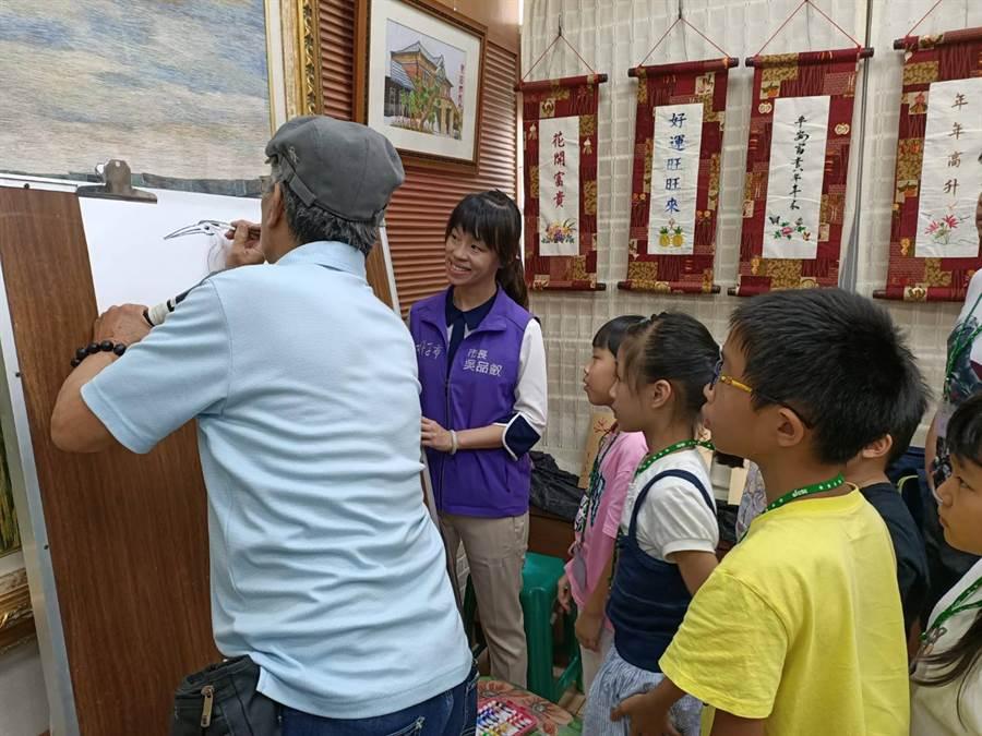 今日蔡龍進手拿水彩筆,一邊闡述畫技,還要一邊畫圖,畫出來的白鷺鷥,型態逼真,眾人看得嘖嘖稱奇。(張毓翎攝)