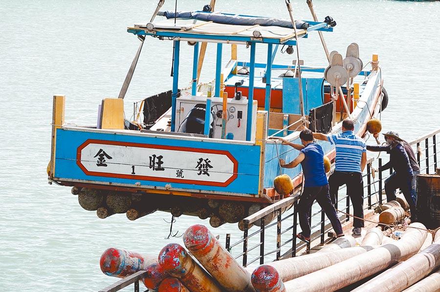 「利奇馬」恐直撲北台灣而來,桃園竹圍漁港停靠不少進港避風的漁船,船東趕在颱風來襲前,請來吊車將漁船吊上岸整修,做好防颱準備。(黃世麒攝)