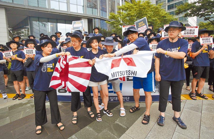 一群南韓大學生7日聚集在首爾的日本三菱集團大樓前,撕毀象徵日本的太陽旗與三菱集團旗幟,抗議日本把南韓從出口優惠「白名單」正式除名。(美聯社)