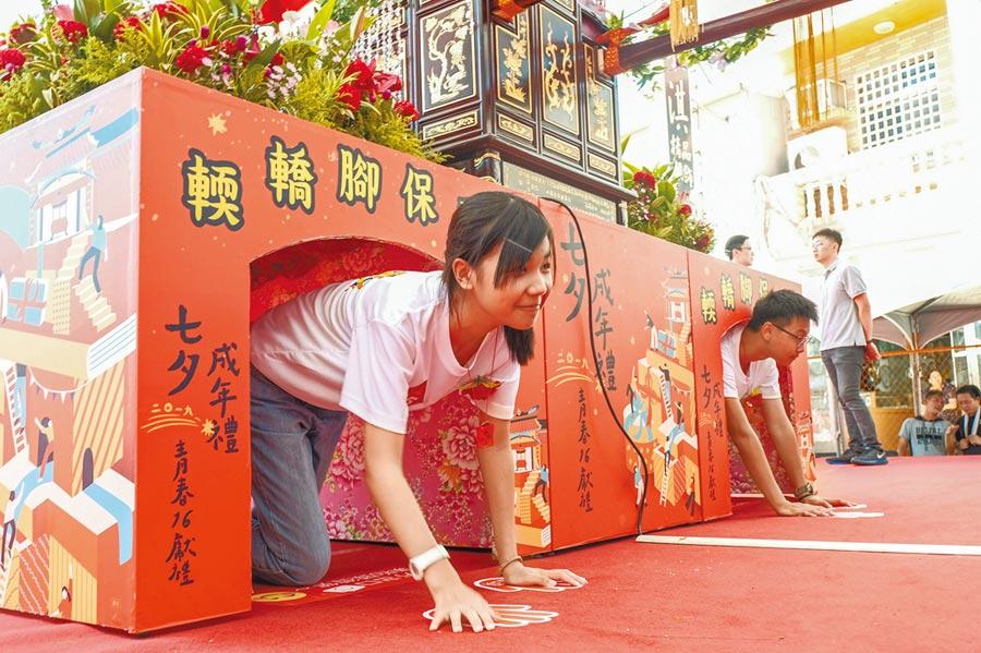 新竹市竹蓮寺是北台灣唯一遵循古禮舉辦七夕成年禮的寺廟,參加成年禮的學生鑽轎底轉大人。(羅浚濱攝)