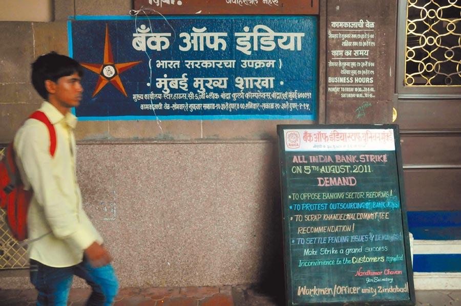 一名行人從印度一家銀行門前走過。(新華社資料照片)