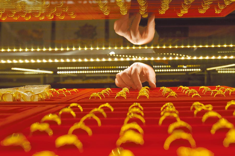 中國人民銀行連續8個月增持黃金。圖為山西太原一金店工作人員正在整理黃金飾品。(中新社資料照片)