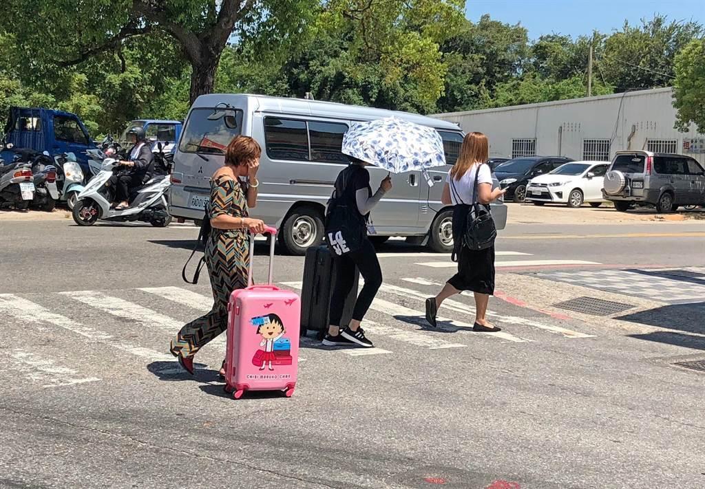 金門高溫讓走在街頭像「逃難」一樣的民眾,大呼「熱死人了!」。(李金生攝)