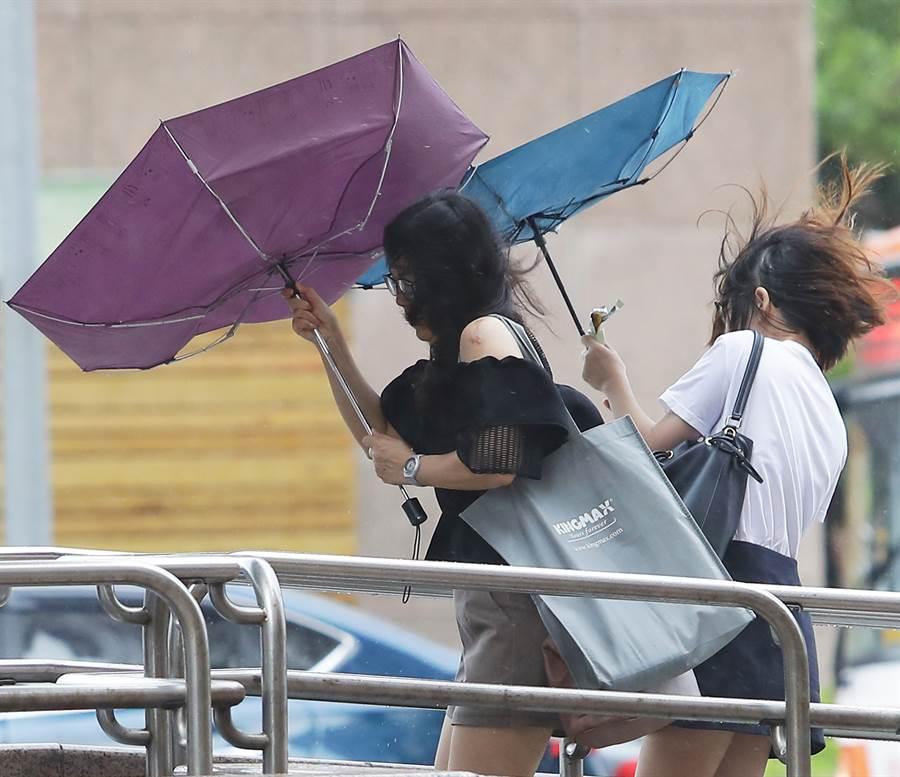 利奇馬撲北台灣,強風讓路人撐的傘也開花了。(季志翔攝)