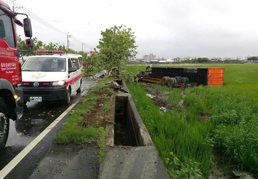 貨櫃車衝到稻田裡,貨櫃傾倒,車頭兩輪朝天、司機被壓在變形駕駛座內。(劉秀芬翻攝)