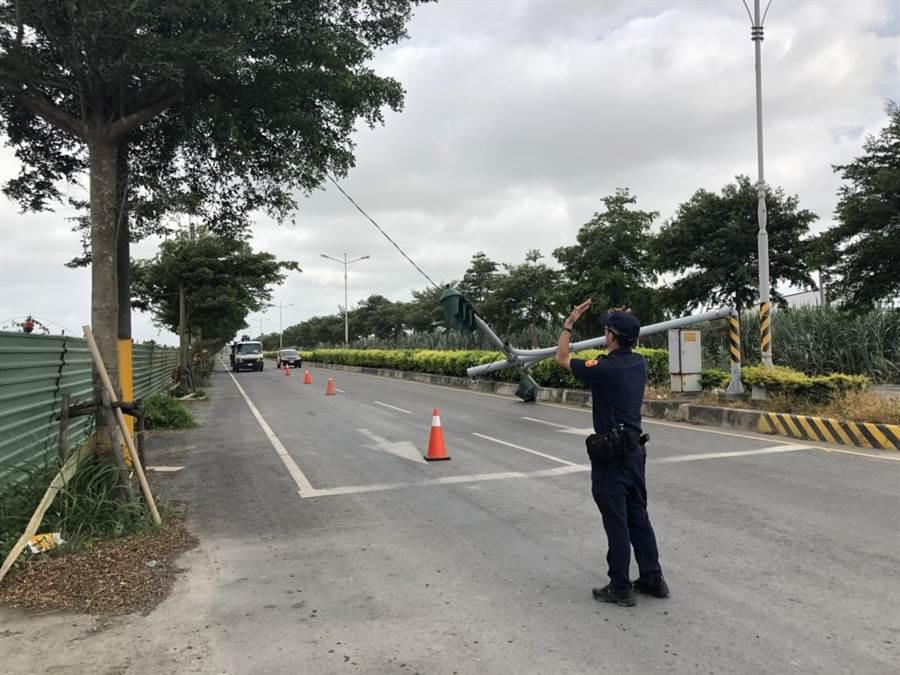 彰化縣二林鎮一處紅綠燈號誌桿,8日下午不敵強颱利奇馬強風吹襲被攔腰吹斷,員警趕緊到現場交通管制。(謝瓊雲翻攝)