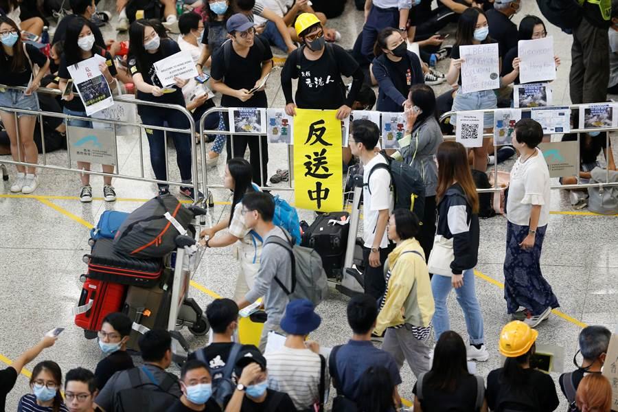 香港反送中抗議群眾在機場集結,號稱「萬人接機」活動,對過往旅客宣揚反送中5大訴求。(圖/路透)