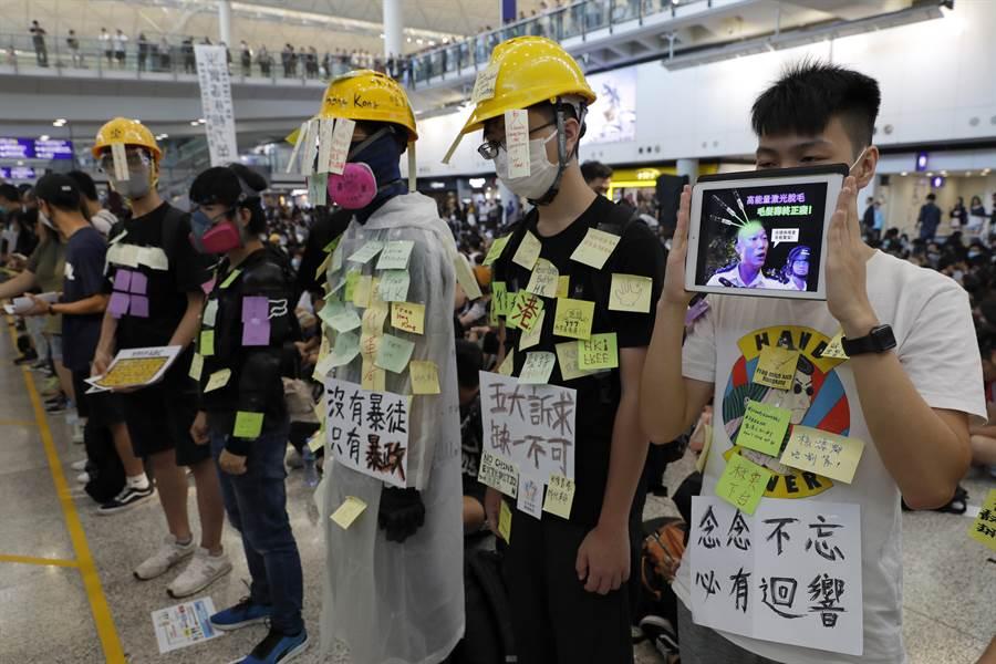 香港抗議群眾號召「萬人接機」活動,有近千人湧入機場大廳,抗議者帶著抗議標語向旅客們表達訴求。(圖/美聯社)