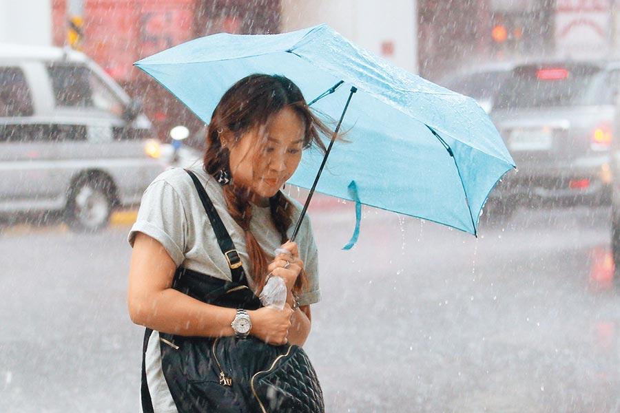颱風「利奇馬」威力持續增強,首當其衝的北台灣8日出現間歇性風雨,民眾撐傘快步過街,仍免不了淋得一身溼。(黃世麒攝)