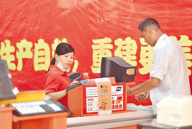 2016年7月29日,福建閩清永輝超市員工為顧客結帳。(新華社)