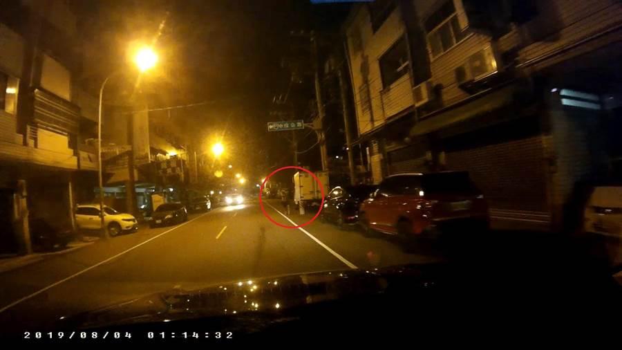 洪父抱著孩童,衝向巡邏車同時舉起左手示意停車。(馮惠宜翻攝)