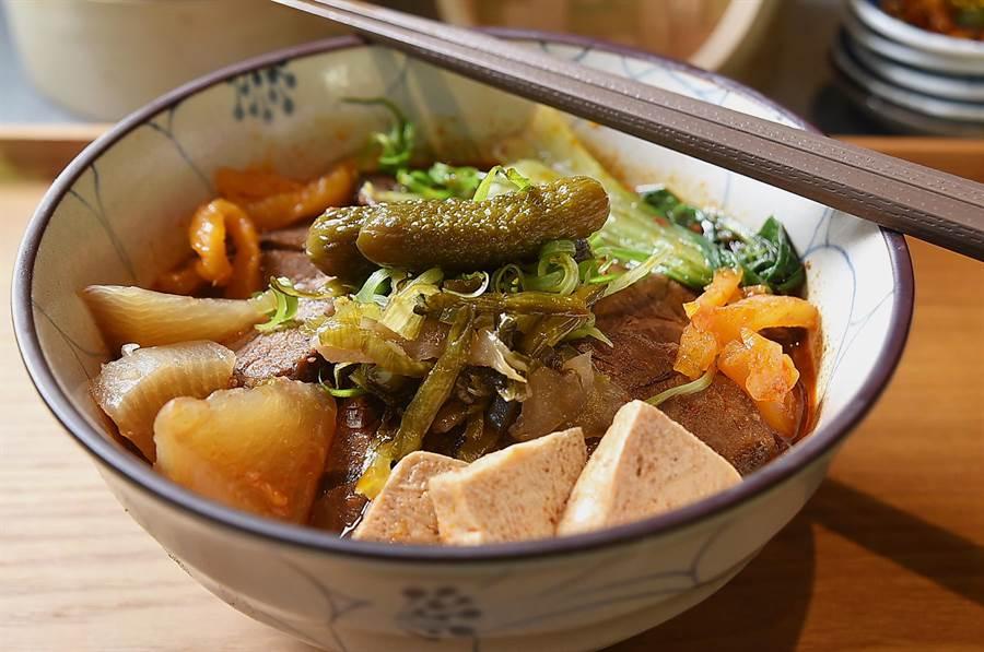 享用〈麻膳堂〉的〈麻辣牛肉麵〉時,把所有配菜倒入碗中,整碗麵的風味口感更加豐富。(圖/姚舜)
