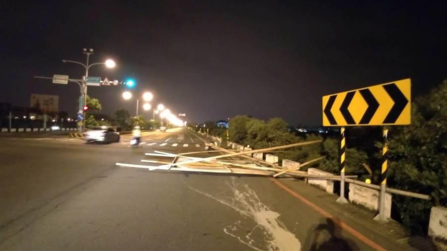 利奇馬颱風掃落路邊鷹架,造成一名女騎士摔車受傷。(程炳璋翻攝)