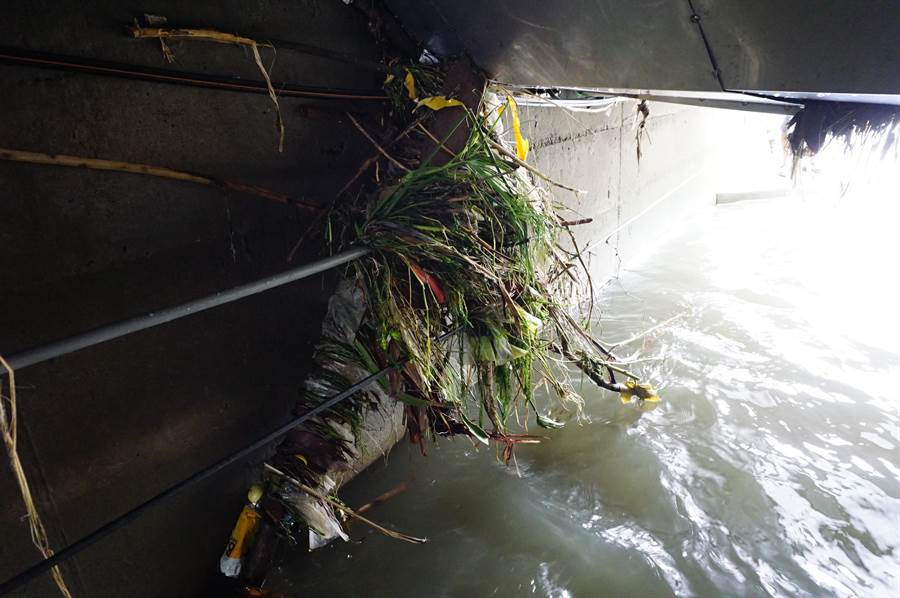 洪水退去後,附掛在灌溉溝旁的管線卡滿雜草垃圾。(王文吉攝)