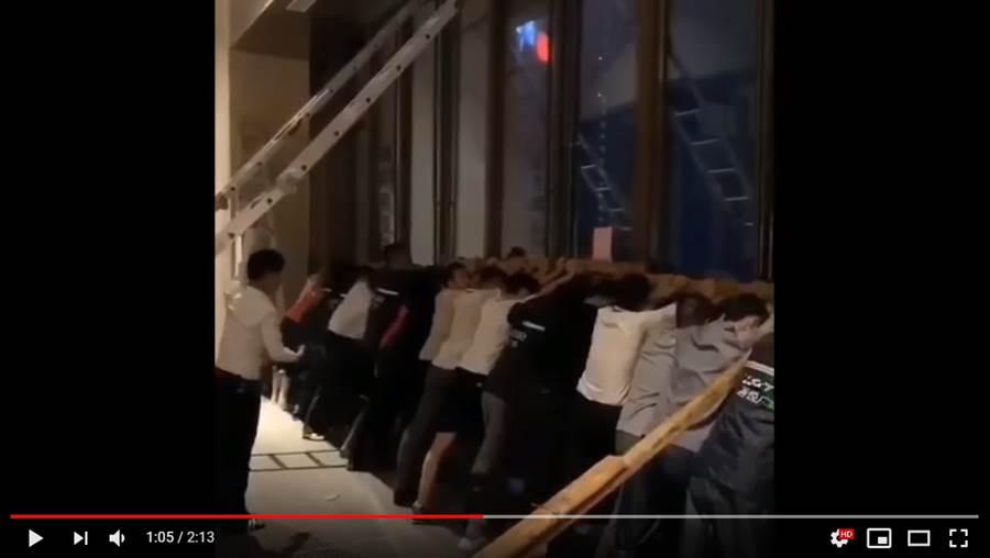 利奇馬狂風橫掃,數十名民眾雙手撐住玻璃大門,防止意外發生 (圖/影片截圖)