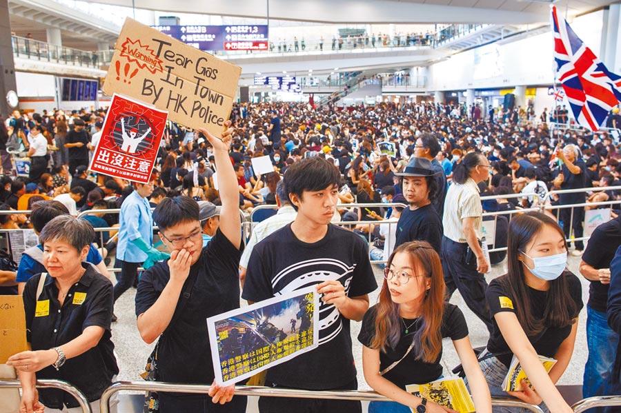 反送中示威者9日在香港國際機場發起「萬人接機」行動,舉牌向入境旅客說明原委。(路透)