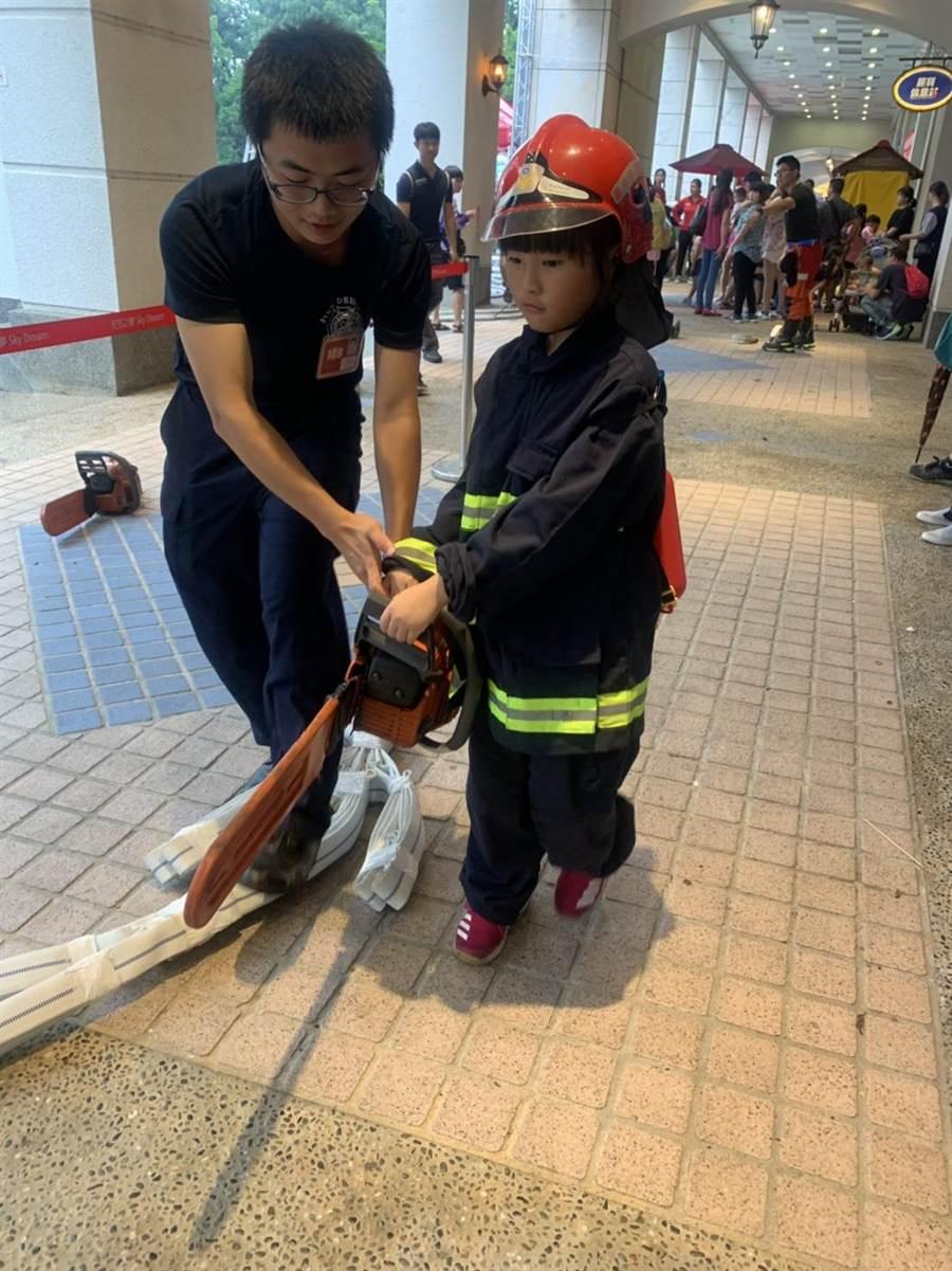 小朋友穿上縮小版消防衣,體驗使用消防設備,模樣可愛。(王文吉翻攝)