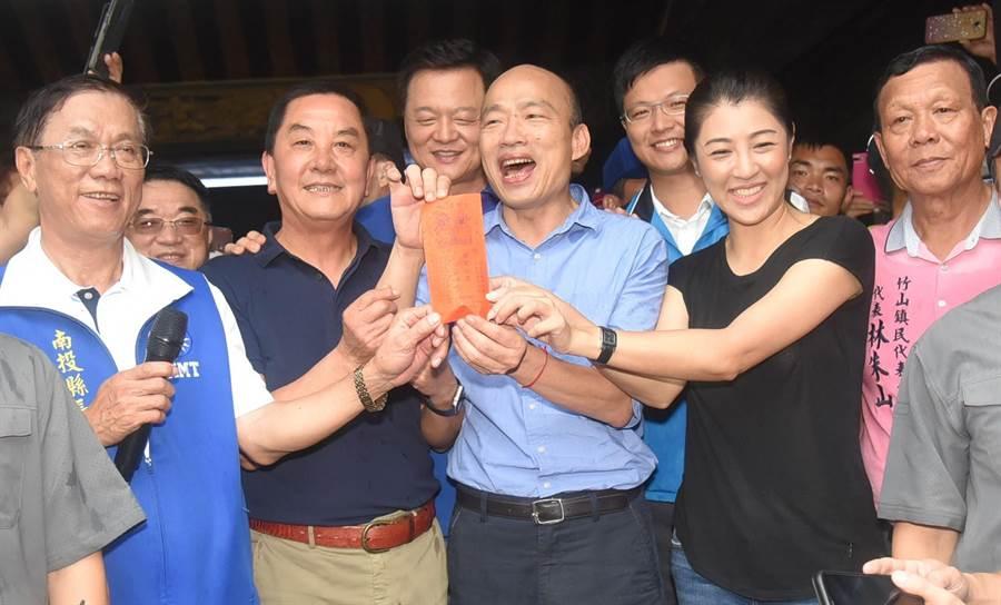 韓國瑜在人潮簇湧下擠進紫南宮,並用高雄市政府名義向紫南宮土地公借600元發財金,希望高雄市的財政越來越好、人民越來越有錢。 (楊樹煌攝)