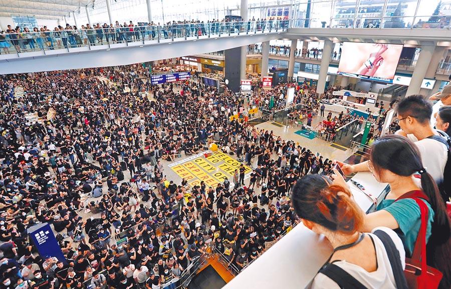 大批反送中群眾10日聚集在香港機場入境大廳參加「萬人接機集會」。這個周末香港許多地區持續有遊行抗議活動,部分示威者占據馬路,築路障癱瘓交通,並與警方發生衝突。(路透)