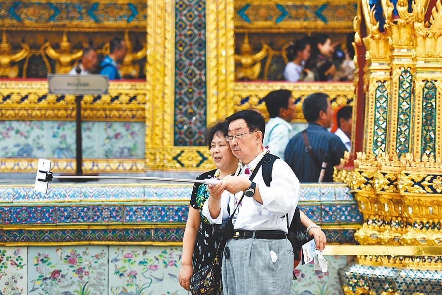 一對陸客夫婦在泰國曼谷大皇宮及玉佛寺景區自拍。(新華社資料照片)