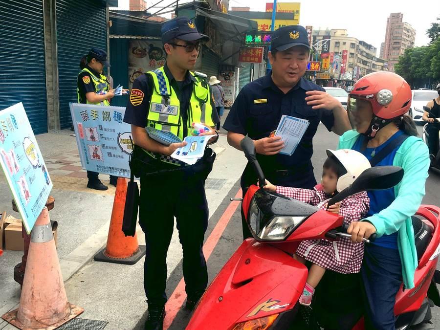 新莊警分局長林武宏(右)率交通組及派出所員警前往市場,宣導「兒童乘坐機車安全」。(吳亮賢翻攝)