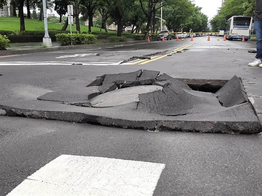 長達約200公分、寬180公分路面破裂,隆起近10公分,地上人孔蓋被「拔起」;建設局經民眾通報,現場派員拉起封鎖線以防過馬路民眾被絆倒。(張妍溱攝)