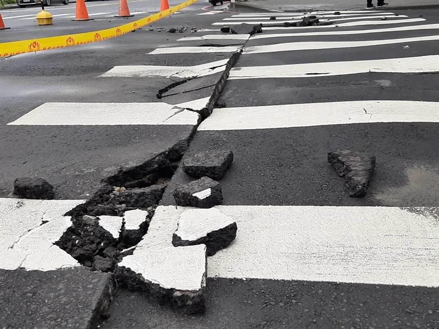 路口斑馬線出現路裂10米長、開口寬最大約30公分,現場拉起封鎖線警戒,建設局通知工程單位進行搶修。(張妍溱攝)
